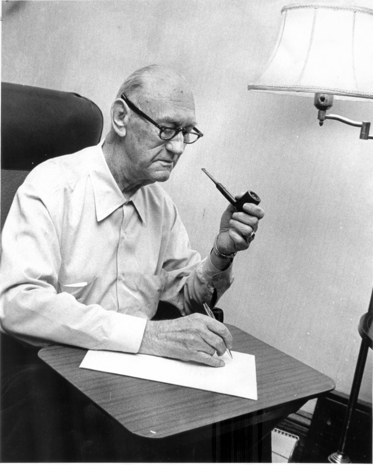 William Baker with pipe and writing